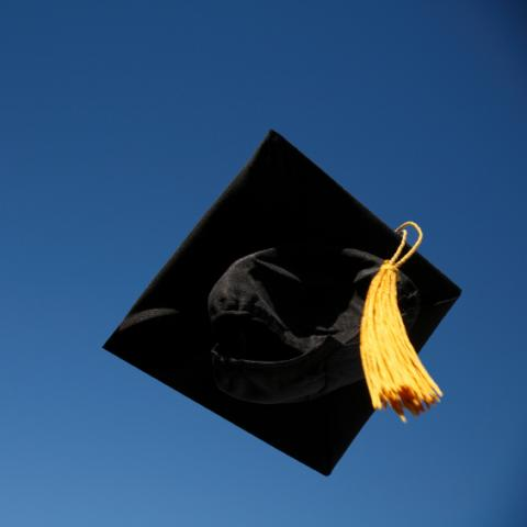 graduation cap in air