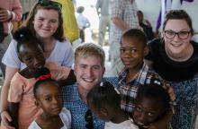 team members with church going kids in haiti