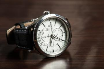 man's watch on wooden table